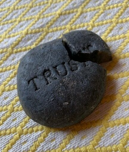 decorative stone with the word trust engraved laying on a yellow fabric