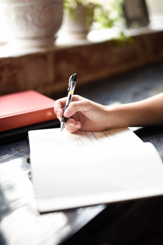 hand holding pen over a diary and a coffee pot next to it